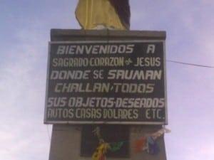 Spiritueller Materialismus - Schild an der Statue Corazon de Jesus Herz Jesu Beten für Auto Haus Dollars